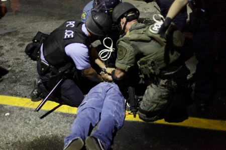 Police in riot gear detain a demonstrator protesting against the shooting of Michael Brown, in Ferguson